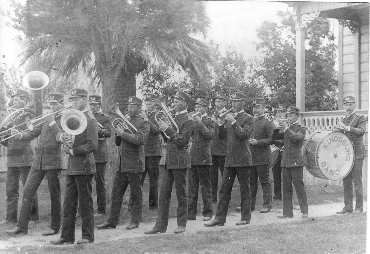 Old Band Marching in Front of Building